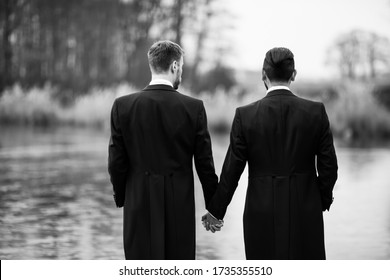 Couple of men holding hands and standing on a wooden pier. Look at the water.
