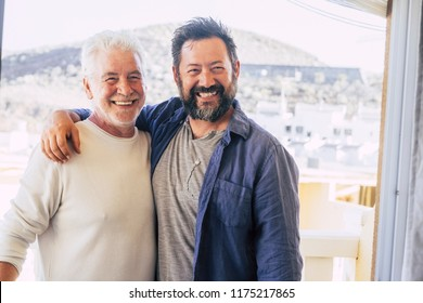 couple of men hugging and stay together in friendship and relationship. father and son different ages smi.ing and look at the camera. portrait of cheerful caucasian people mixed generations enjoy life