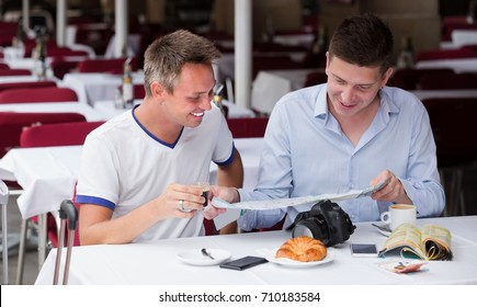 Couple of men tourists using map and drinking coffee with bakery