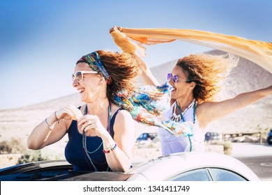Couple of middle age caucasian woman cheerful and laughing enjoying the travel and the vacation with convertible car and playing with the wind for freedom lifestyle concept