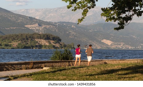 Couple of middle aged man and woman taking a run at a park, before sunset, at the banks of a lake
