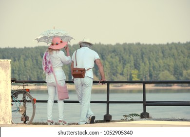 couple middle-age in white dressed with the hats in hot morning on the quay of Danube in Vidin; the lady protects herself from the sun with a retro lace white parasol - Bulgaria