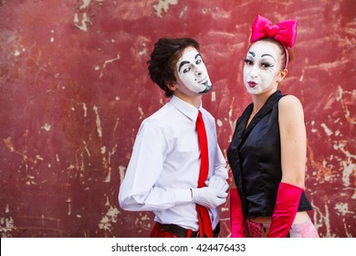 Couple mimes cute pose in front of a red wall.