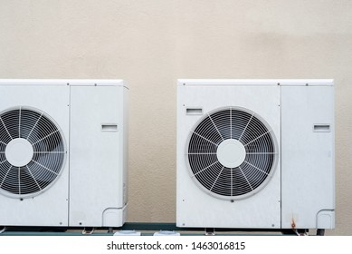 A couple mini-split air conditioner condensers outside, with beige wall in background