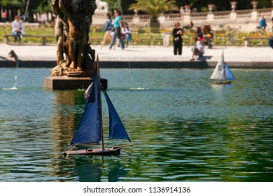 a couple of model ships navigating in the fountain of luxembourg garden, in paris