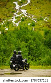 Couple of motorcyclist and adventure motorbike on green summer norwegian nature, at mountains waterfall river. Motorcycle trip. World Traveling