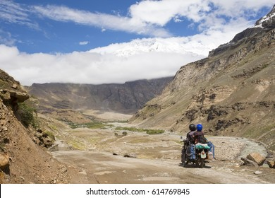 Couple Motorcyclist on a mountainous road, cold overcast weather, bright sun. Extreme sport, active lifestyle, adventure touring concept. Snowy high mountains, dirt roads.