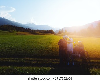 A couple of motorcyclists pose of the incredible beauty of the sunset. Sun rays and glare. Riders in love guy and girl. Bikers and their bike. destination. Mountains of Slovenia. Copy space