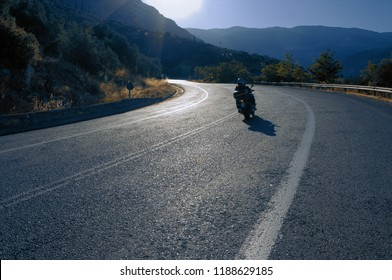 couple of motorcyclists travelling on curve road of Greece
