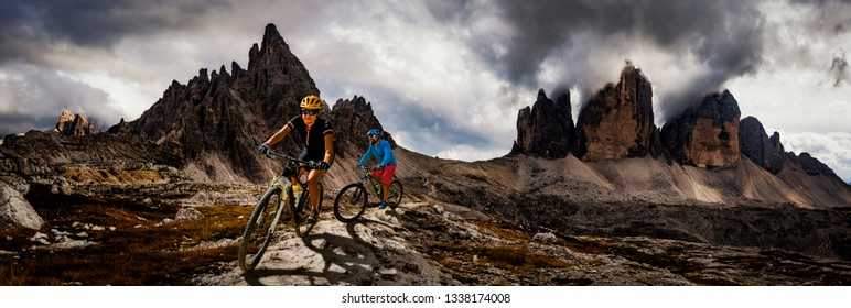Couple mountain bike riders on electric bike, e-mountainbike rides up mountain trail. Woman and Man riding on bike in Dolomites mountains landscape. Cycling e-mtb trail track. Outdoor sport activity.