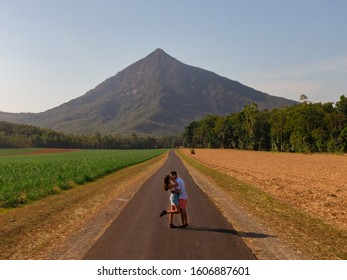 Couple with mountain landscape with sugar cane fields foreground. Dramatic DRONE aerial view of fields, trees, green forest, farm, mountains & road. Romantic shot in Walsh's Pyramid, Cairns, Australia
