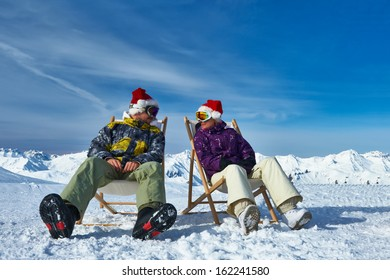 Couple at mountains in Santa hats celebrating christmas, Meribel, Alps, France