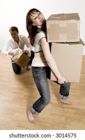 couple moving in apartment - woman carrying all boxes