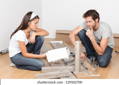 Couple moving in assembling bed furniture with problems and difficulties. Young interracial couple in new home. Asian woman, Caucasian man.