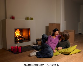 Couple with moving boxes, fire place