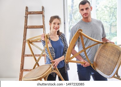 Couple moving or moving carries chairs in the new apartment or new home