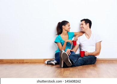 couple moving into empty new home sitting on floor together and drinking coffee