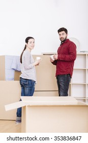 couple moving into empty new home between boxes together and drinking coffee