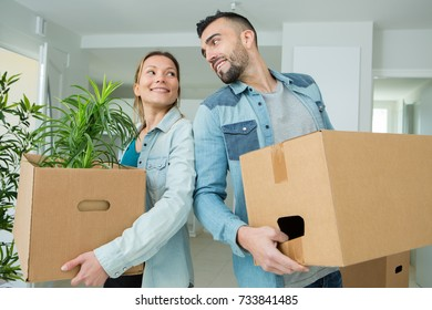 couple moving into a new house carrying cardboard boxes