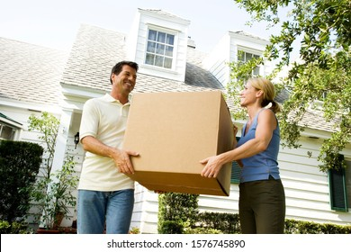 Couple moving into their new home, carrying a packing box