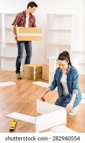 Couple moving in new home house. Unpacking boxes and assembling furniture.