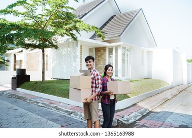 couple moving to their new house holding cardboard box and standing in front of house
