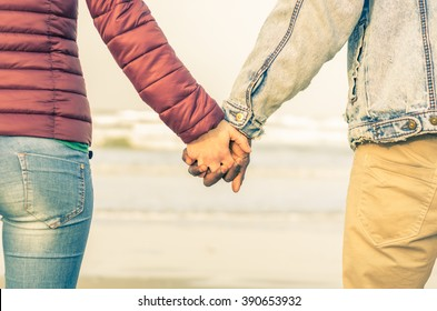 Couple of multiethnic lovers hand in hand to the sea - caucasian and black people - love, multiracial, lifestyle and nature concept