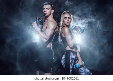 Couple of muscular young people doing exercises with dumbbells. Fitness, bodybuilding. Active, healthy lifestyle.