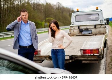 Couple near broken car on a roadside.