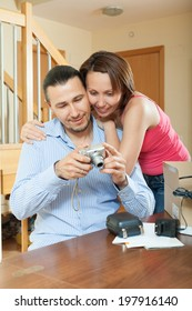 couple with new compact digital camera at home