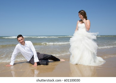 couple of newlyweds playing on the beach sand after the wedding ceremony