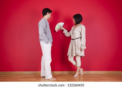 couple next to a red wall looking to a color paint palette (selective focus)