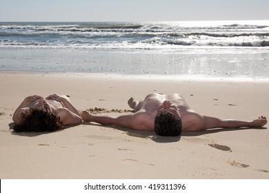 Couple nudist laying on beach under deep blue sky