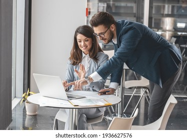 Couple of office workers discuss about new company project.They sitting at the desk and using computer.