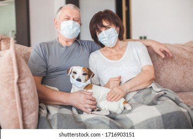 Couple old aged senior people at home with seasonal winter cold illness disease sit down on the sofa. Elderly couple in medical masks during the pandemic Coronavirus CoVid-19
