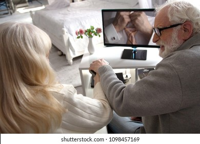 Couple of old grandparents with white hair watching film together in morning. Elderly couple holding TV remote together switching channels in their bedroom.