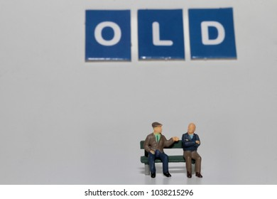 couple of old men talking on a bench in miniature