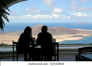 A couple of old people, a man & woman, dreaming watching at a tropic island throuth a cafe window