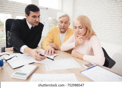A couple of old people at a reception with a realtor. They are satisfied with the service. The realtor in a black suit is sitting next to him. They together discuss the forms that lie before them.