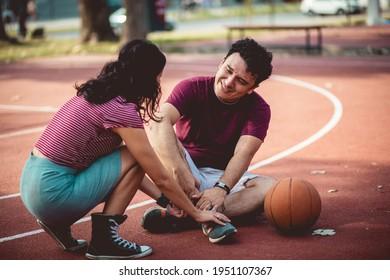 Couple on basketball court. Injury.