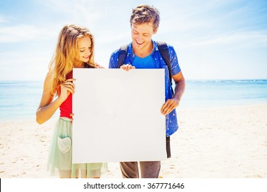 couple on a beach holding blank poster