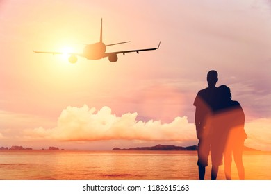 A couple on the beach looking at a airplane over the sea during sunset
