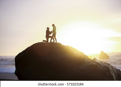 A couple on the beach proposing