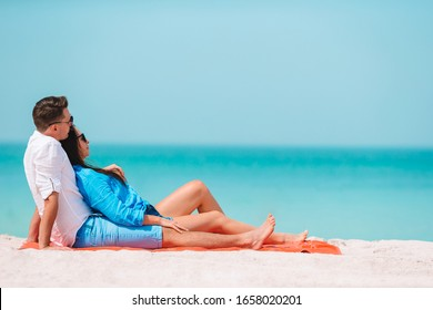 Couple on the beach relax and look at he sea
