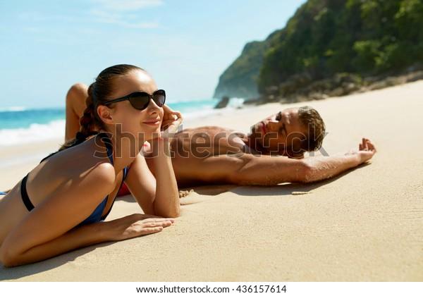 Pareja En La Playa En Verano. Gente Romántica Enamorada Relajándose En Arena, Disfrutando De Vistas Al Mar. Feliz Hombre, Hermosa Mujer En Vacaciones De Verano De Luna De Miel En Luxury Resort. Relaciones, Relax de verano
