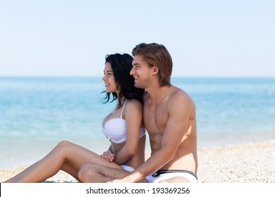 Couple on beach summer vacation, young man and woman embracing smile looking side to copy space, concept travel