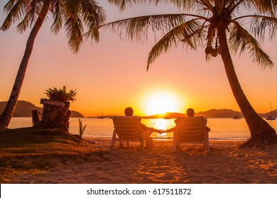 Couple on the beach at sunset, holding hands - warm color