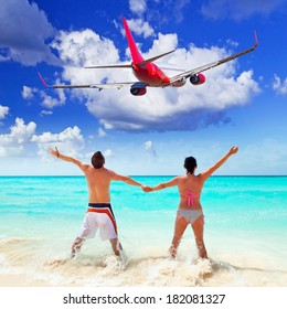 Couple on the beach watching flying aircraft