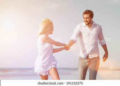 Couple on beach in white clothing running down on vacation or honeymoon