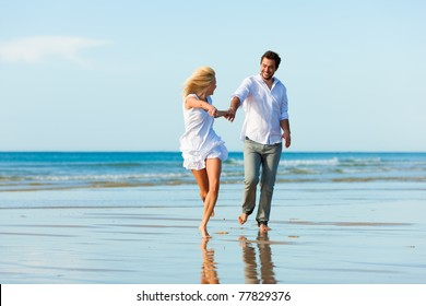 Couple on the beach in white clothing running down, they might be on vacation or even honeymoon